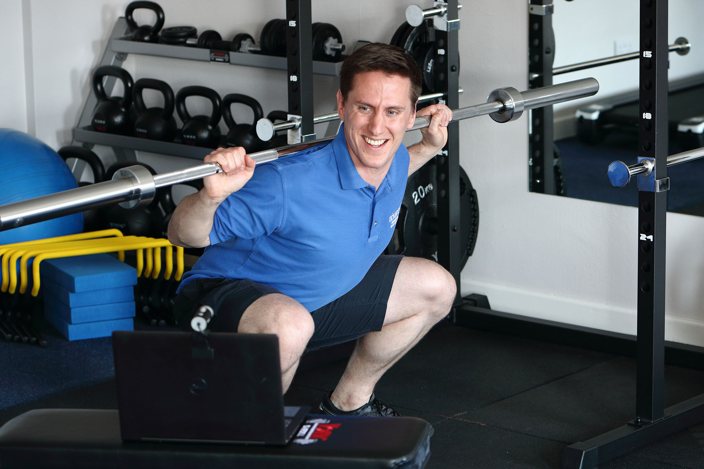 Physio demonstrating a squat with a bar during an online physio consultation